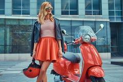 Seksowna elegancka blondynki dziewczyna jest ubranym czerwoną spódnicę i skórzana kurtka czarni okulary przeciwsłoneczni i, trzym zdjęcie royalty free
