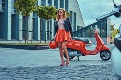 Seksowna elegancka blondynki dziewczyna jest ubranym czerwoną spódnicową czarną skórzaną kurtkę i okulary przeciwsłonecznych, chw fotografia royalty free