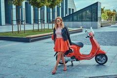 Seksowna elegancka blondynki dziewczyna jest ubranym czerwoną spódnicową czarną skórzaną kurtkę i okulary przeciwsłonecznych, chw zdjęcie stock