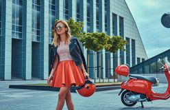 Seksowna elegancka blondynki dziewczyna jest ubranym czerwoną spódnicową czarną skórzaną kurtkę i okulary przeciwsłonecznych, chw obraz royalty free