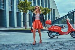 Seksowna elegancka blondynki dziewczyna jest ubranym czerwoną spódnicową czarną skórzaną kurtkę i okulary przeciwsłonecznych, chw obrazy stock