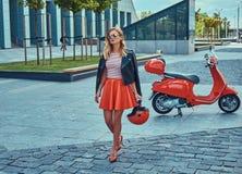 Seksowna elegancka blondynki dziewczyna jest ubranym czerwoną spódnicową czarną skórzaną kurtkę i okulary przeciwsłonecznych, chw zdjęcia royalty free