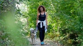 Seksowna kędzierzawa dziewczyna chodzi psa na smyczu zdjęcie wideo