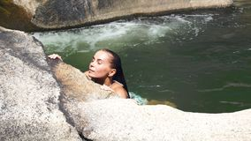 Seksowna kobieta cieszy się kąpanie w jasnej wodzie w kamienistej rzece Piękna kobieta relaksuje podczas gdy pływający w termiczn zbiory wideo