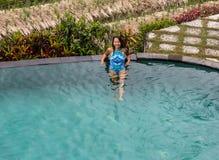 Seksowna kobieta cieszy się słońce przy nieskończoności lata pływackim basenem przy luksusowym kurortem fotografia stock