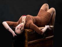 Seksowna kobieta kłaść na drewnianej klatce piersiowej Obraz Stock