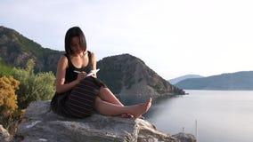 Seksowna kobieta pisze w notesie siedzÄ…cym boso wysoko na skale nad morzem zbiory wideo