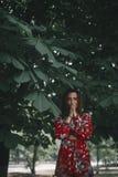 Seksowna kobieta pod kasztanem dziewczyna ubierał w czerwonym kombinezonie w tropikalnym ornamencie wzorcowy ip pozować Zdjęcie Royalty Free