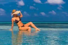 Seksowna kobieta w bikini w basenie, ogląda dennego tło w Maldives Zdjęcie Stock