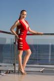 Seksowna kobieta w oszałamiająco czerwieni sukni, szpilkach na hotelowym ` s balkonie na niebieskiego nieba tle i fotografia stock
