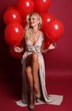 Seksowna kobieta z blond kędzierzawym włosy jest ubranym elegancką suknię, trzyma mnóstwo czerwonych lotniczych balony fotografia stock