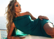 Seksowna kobieta z blondynem wewnątrz greeen smokingowy pozować na jachcie Obrazy Stock