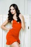 Seksowna kobieta z długie włosy jest ubranym czerwieni suknią z fala Fryzuje fryzurę Zdjęcie Stock