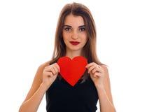 Seksowna młoda brunetki kobieta z czerwonym sercem w ręk pozować odizolowywam na białym tle Świątobliwy walentynki ` s dnia pojęc Obrazy Royalty Free