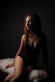 Seksowna młoda piękna brunetki kobieta w zmysłowej czarnej bieliźnie, siedzi na białej ławce z futerkiem Obrazy Stock