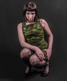 Seksowna militarna dziewczyna w skulonej pozyci Zdjęcia Royalty Free
