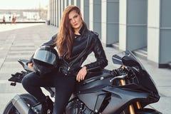 Seksowna rowerzysta dziewczyna pozuje na jej superbike na zewnątrz budynku zdjęcie royalty free