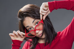 Seksowna 20s kobieta patrzeje nad jej zabawy czerwieni szkłami Zdjęcia Stock