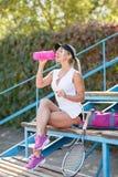 Seksowna sport kobieta w nakrętce z butelką woda na stadium tle, tła piękna błękitny pojęcia zbiornika kosmetyczny głębii szczegó Obrazy Stock