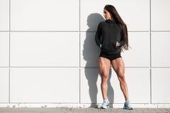 Seksowna sportowa kobieta z dużymi kwadratami Mięśniowa dziewczyna pozuje plenerowe, mięśniowe nogi, Obrazy Royalty Free