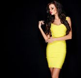 Seksowna szczupła brunetka pozuje w kolor żółty sukni zdjęcie stock