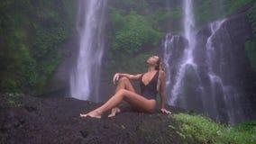 Seksowne młodych kobiet pozy pod wielką tropikalną kaskadą, utrzymań oczy zamykający, model w czarnym swimsuit relaksują nawadnia zbiory