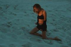 Seksownej blondynki z włosami młoda kobieta pozuje w piaskach pustynia zaświecał czerwonym położenia słońca światłem Zdjęcie Stock
