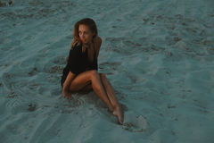 Seksownej blondynki z włosami młoda kobieta pozuje w piaskach pustynia zaświecał czerwonym położenia słońca światłem Zdjęcia Royalty Free