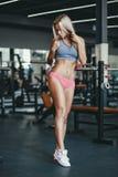 Seksownej sprawności fizycznej blondynki szczęśliwa dziewczyna w sport odzieży z perfect ciałem w gym pozuje i ono uśmiecha się Zdjęcie Royalty Free