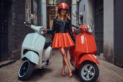 Seksowny blondynki dziewczyny być ubranym elegancki odziewa w okularach przeciwsłonecznych i hełmie stoi na starej wąskiej ulicie zdjęcia royalty free