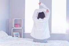 Seksowny brunetki obsiadanie na jej łóżku Obrazy Stock