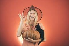 Seksowny czarownica wampira pojęcie Czarny kot siedzi na bani Wyrażeniowa twarz - zdziwiona kobieta Atrakcyjna wzorcowa dziewczyn obrazy stock