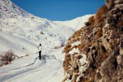 Seksowny kobieta spacer w śnieżnej drodze w górach Fotografia Royalty Free