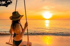 Seksowny kobiety odzieży bikini i słomiany kapelusz huśtamy się huśtawki przy tropikalną plażą na wakacje przy zmierzchem Dziewcz obraz royalty free