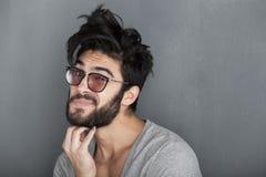 Seksowny mężczyzna naciera jego brodę przeciw ścianie Zdjęcia Royalty Free