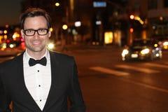 Seksowny mężczyzna w smokingu i łęku krawacie pozuje w miasto ulicach przy nocą Zdjęcia Stock