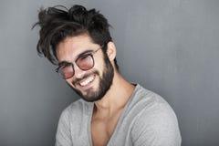Seksowny mężczyzna z brody ono uśmiecha się duży przeciw ścianie Zdjęcia Stock