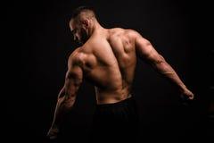 Seksowny mężczyzna z perfect mięśniowym plecy na czarnym tle Sportowy i bodybuilding ćwiczenie żarówki eco elektryczne linie wład obraz royalty free