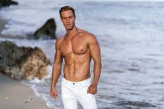 Seksowny mi??niowy facet w biel spodniach i bez koszuli pozowa? na tropikalnej piaskowatej pla?y, ocean fale przy t?em obraz royalty free