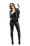 Seksowny piękno jest ubranym czarną skórę i buty trzyma pistolecika z dwa pokoju ręki palcowym gestem Fotografia Royalty Free