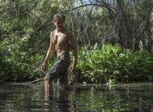 Seksowny przygoda mężczyzna watuje przez bagna fotografia stock