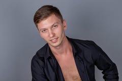 Seksowny przystojny mężczyzna jest ubranym czarnego koszulowego obsiadanie na rzemiennej kanapie Wygoda i relaks zdjęcie stock