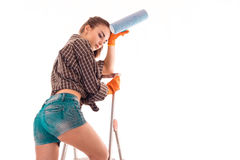 Seksowny zmęczony brunetki kobiety budowniczy w mundurze z farba rolownikiem w jej rękach robi reovations odizolowywającym na bia Zdjęcie Stock