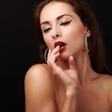 Seksuele jonge vrouw met vinger dichtbij rode lippen royalty-vrije stock fotografie