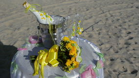 Sektflasche im Eiseimer, in zwei Gläsern und im Hochzeitsdekor auf dem Strand stock footage