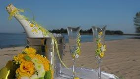 Sektflasche im Eiseimer, in zwei Gläsern und im Hochzeitsdekor auf dem Strand stock video