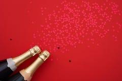 Sektflaschen mit Konfettiherzen auf rotem Hintergrund Kopieren Sie Raum, Draufsicht lizenzfreie stockfotografie