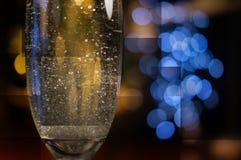 Sektglas und unscharfer Girlandengeometriehintergrund lizenzfreies stockbild