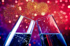 Sektkelche mit goldenen Blasen auf rotem und purpurrotem hellem bokeh und Feuerwerksscheinhintergrund Stockfoto