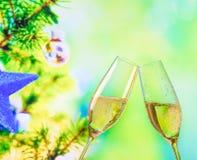 Sektkelche mit goldenen Blasen auf Weihnachtsbaum-Dekorationshintergrund Stockfotografie